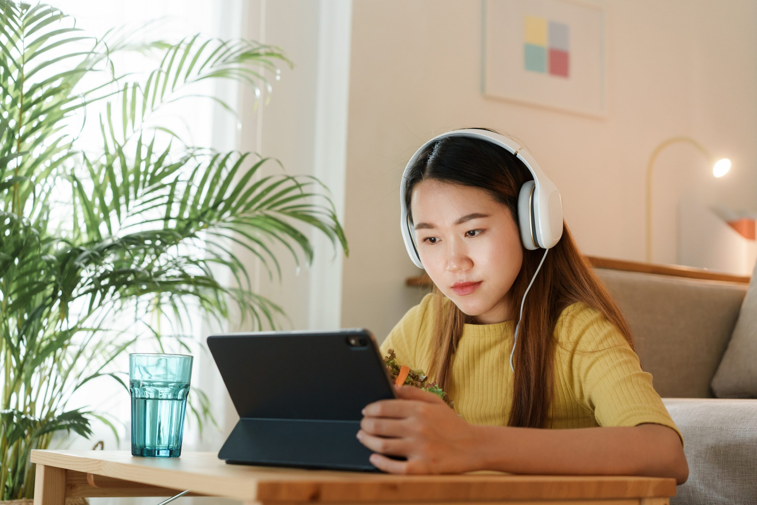 beautiful Asian young woman using a tablet and eat salad for lun